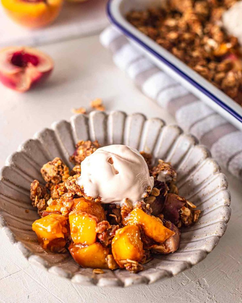 Close up of individual serving of peach crumble topped with dairy free ice cream