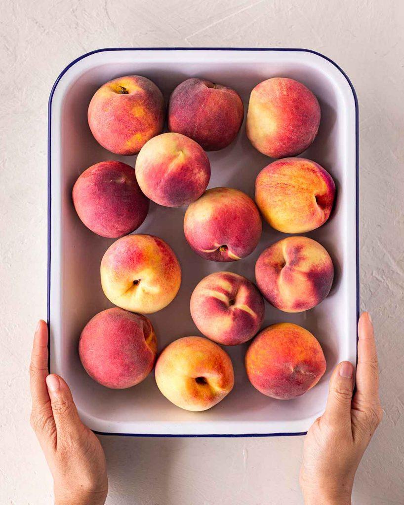 Flatlay of medium size peaches in casserole dish.