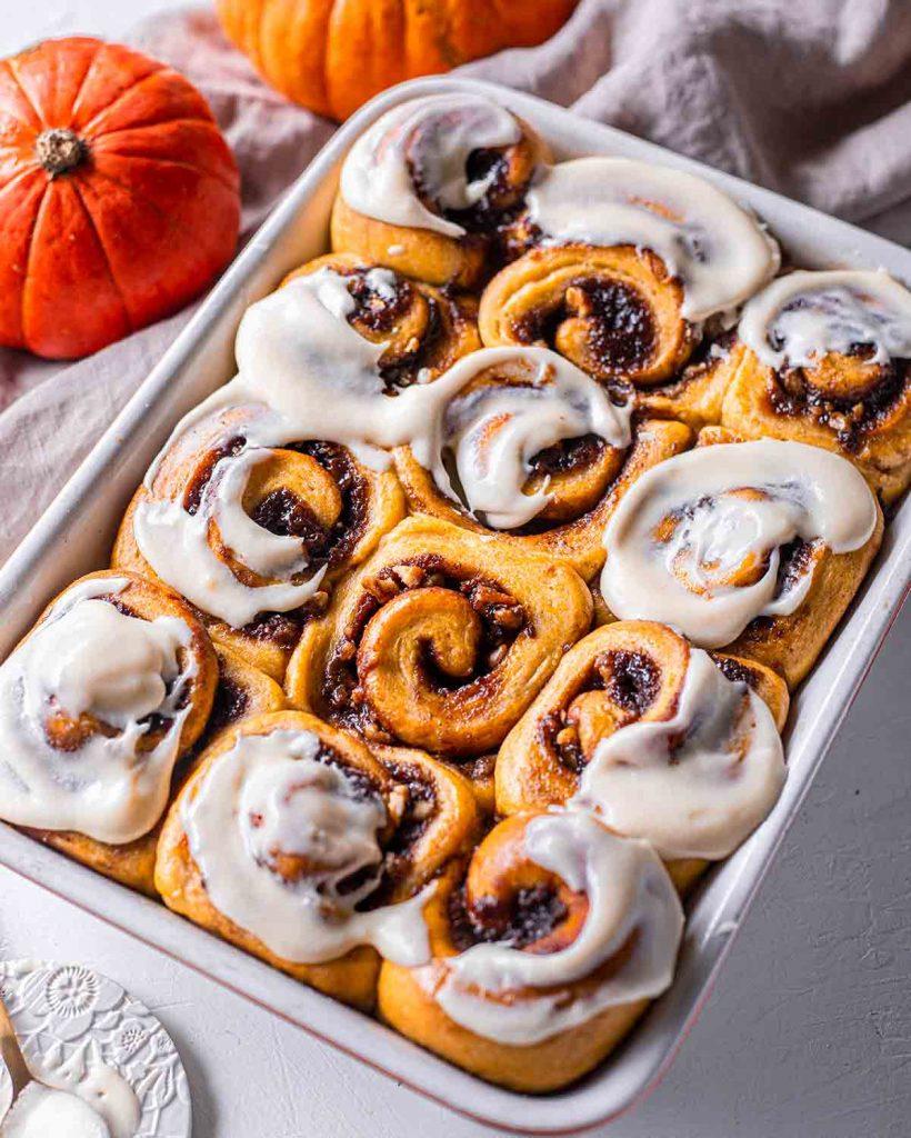 Side angle of pumpkin cinnamon rolls in baking tray.