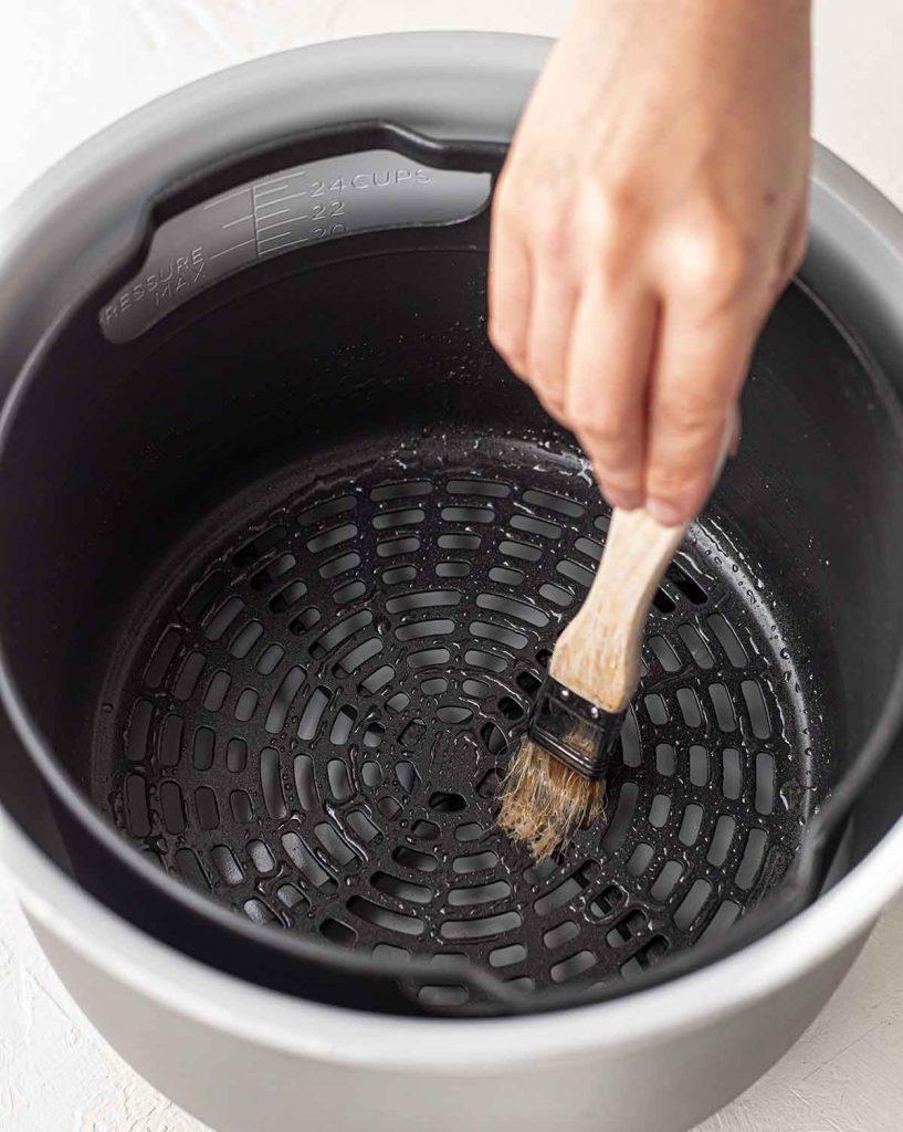 Hand brushing oil insider an air fryer baskest