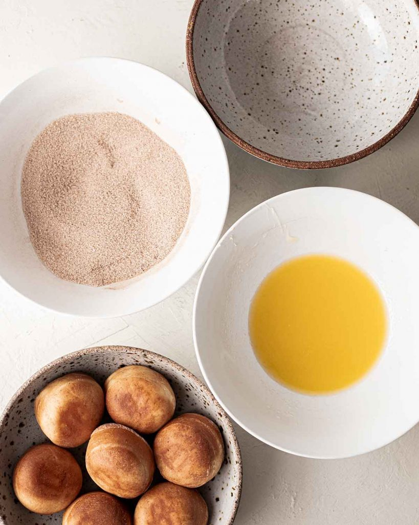 Flatlay of four bowls showing the undressed donuts, a bowl of melted vegan butter, a bowl of cinnamon sugar and an empty bowl for the final donuts