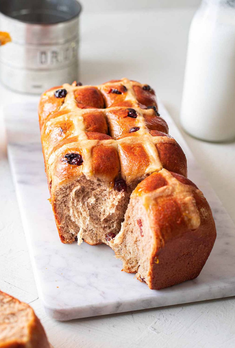 Vegan brioche hot cross buns loaf on a marble serving platter. One hot cross bun has been taken away revealing the feathery and buttery texture.