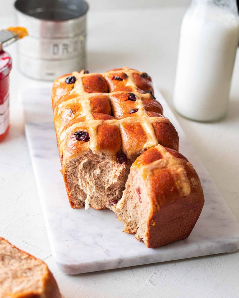 Vegan brioche hot cross buns loaf on a marble serving platter. One hot cross bun has been taken away revealing the feathery and buttery texture.