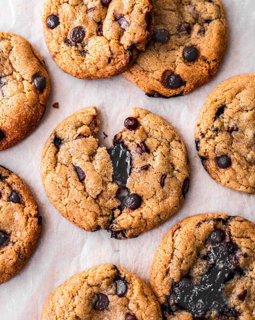 Flatlay of vegan chocolate chip cookies on a piece of baking paper. One cookie is broken in half revealing hot fudge centre.