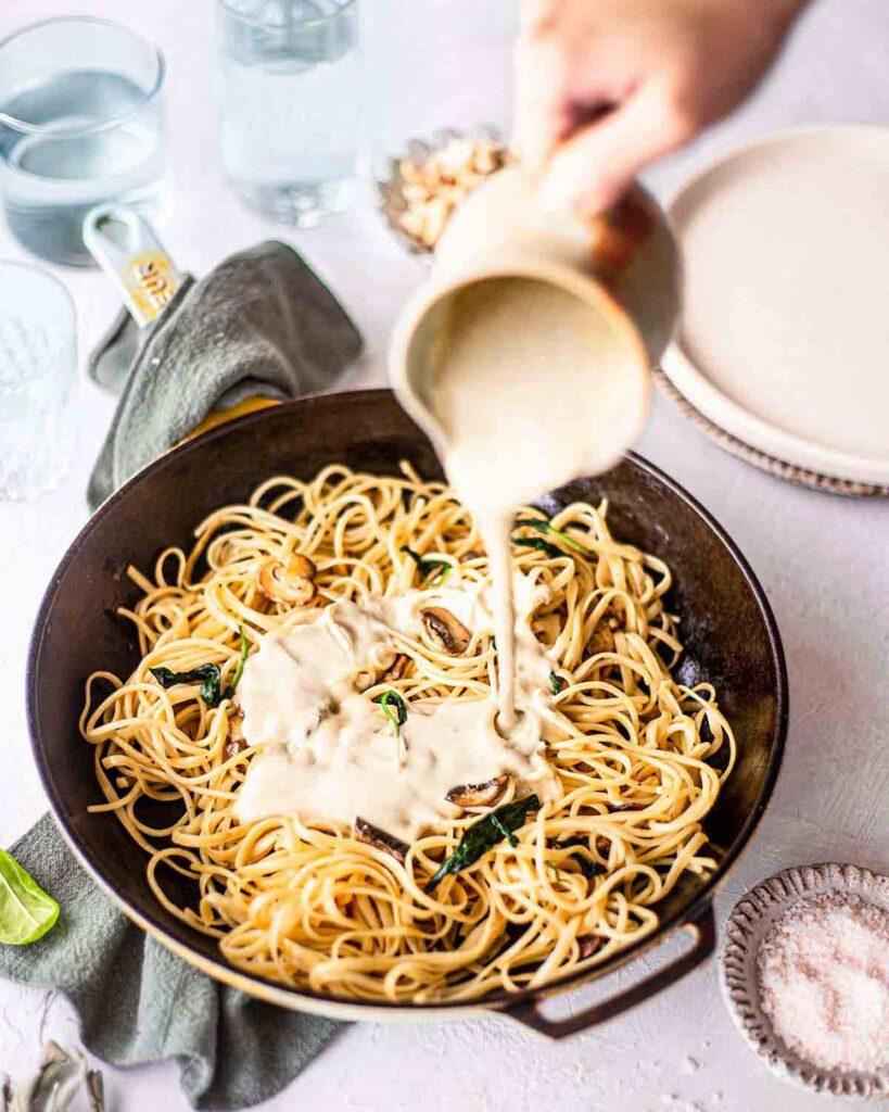 Easy vegan alfredo sauce poured over pasta in skillet