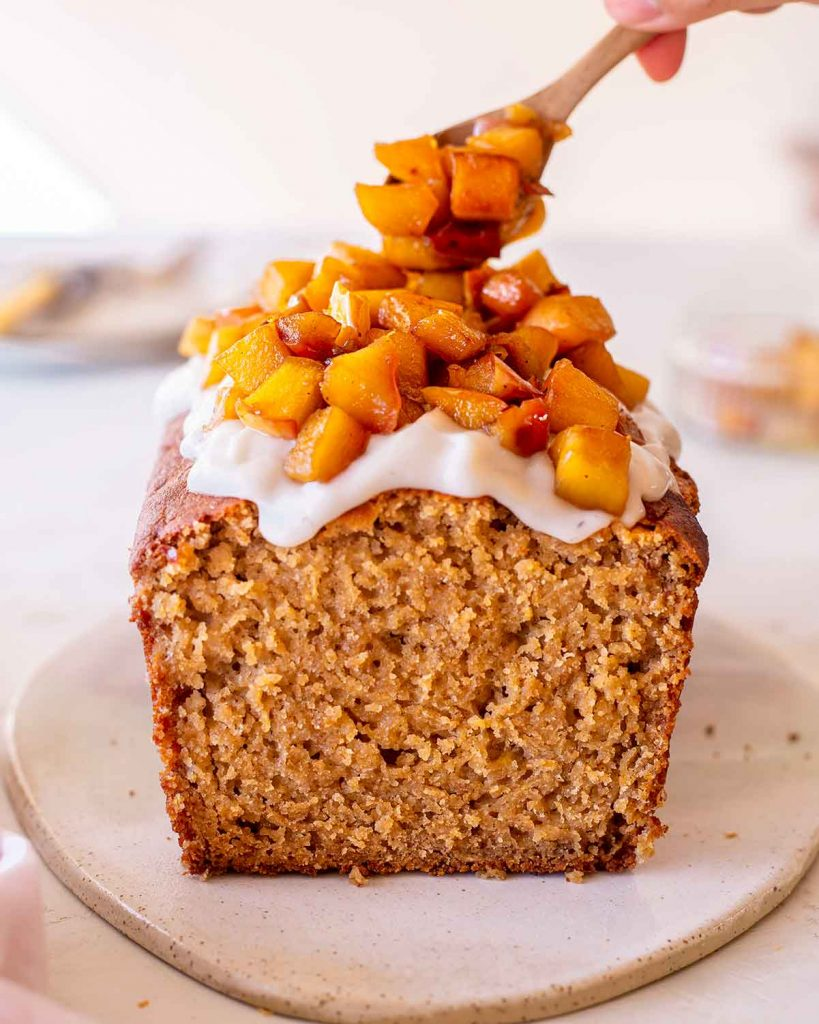 Gluten free vegan apple bread topped with coconut yoghurt and caramelised apples. A bamboo spoon is topping the apple bread with more apple pieces.