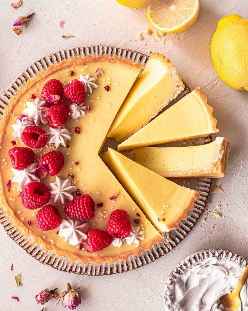 Lemon tart on plate with a few slices coming out showing texture