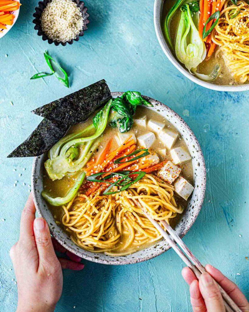 Hand holding chopsticks getting ready to easy vegan ramen