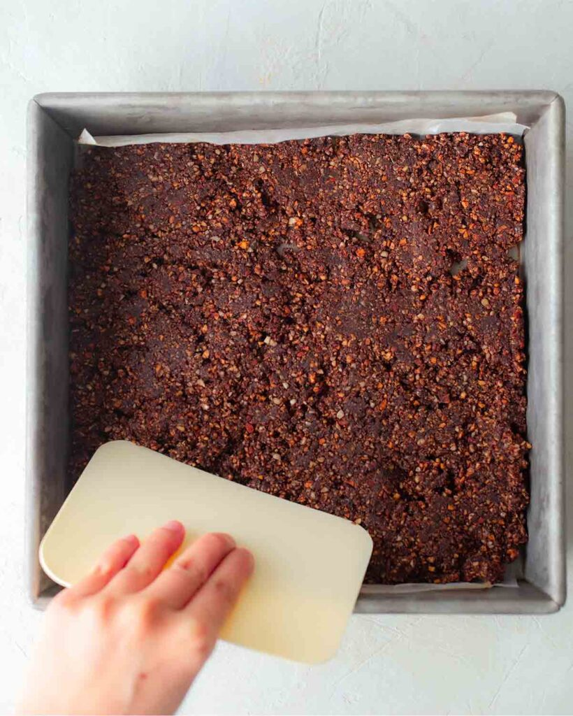 Hand pressing the chocolate layer for the vegan raspberry slice