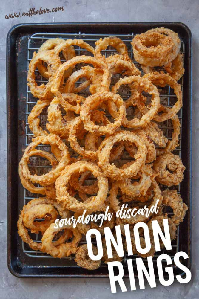 Crispy golden sourdough discard onion rings on a baking tray and cooling rack