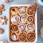 Vegan gingerbread cinnamon rolls in baking tray with gingerbread cut out cookies and hot chocolate surrounding it.