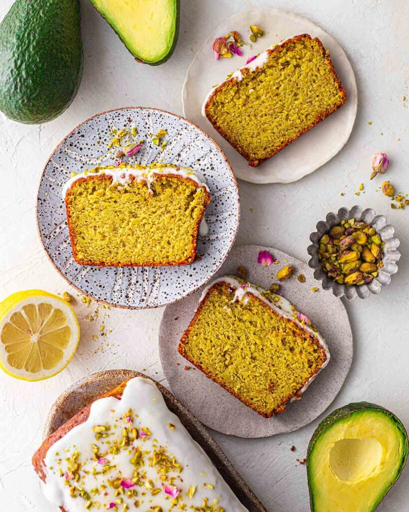 Flatlay of pistachio cake slices on rustic plates with ingredients on the sides