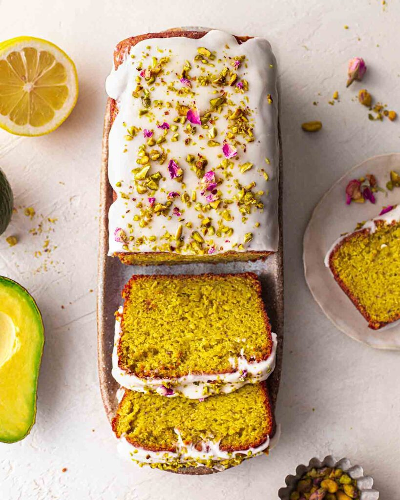Bird's eye view of decorated pistachio cake with a few slices coming out showing subtle green colour and fluffy texture