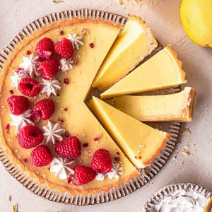 vegan lemon tart with a few slices cut out of it