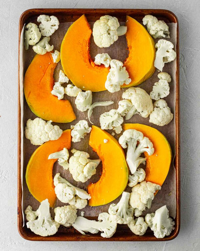 Lined baking tray with raw cauliflower and pumpkin