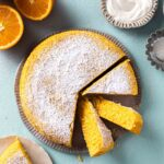 Simple vegan orange cake dusted with icing sugar on plate with a few slices coming out showing beautiful orange hue