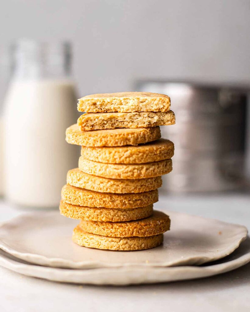Close up of stack of cookies. Two cookies on top are in half revealing crumbly and golden texture.
