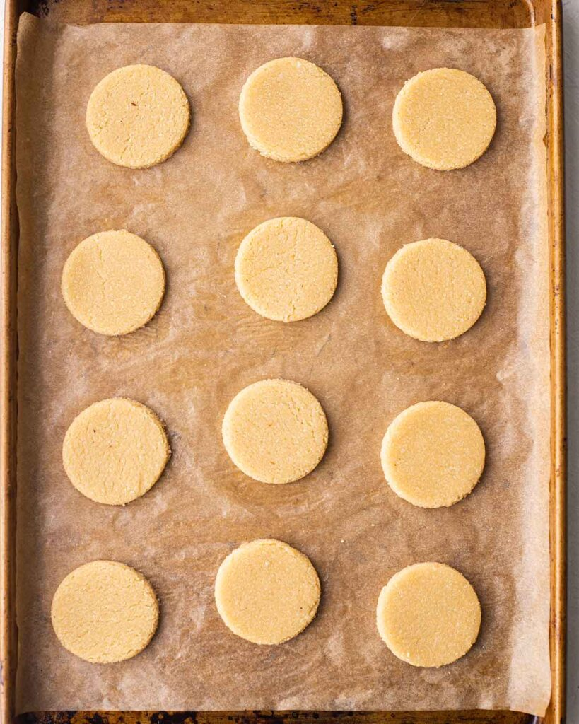 Lined baking tray of 12 unbaked round vegan gluten free shortbread.
