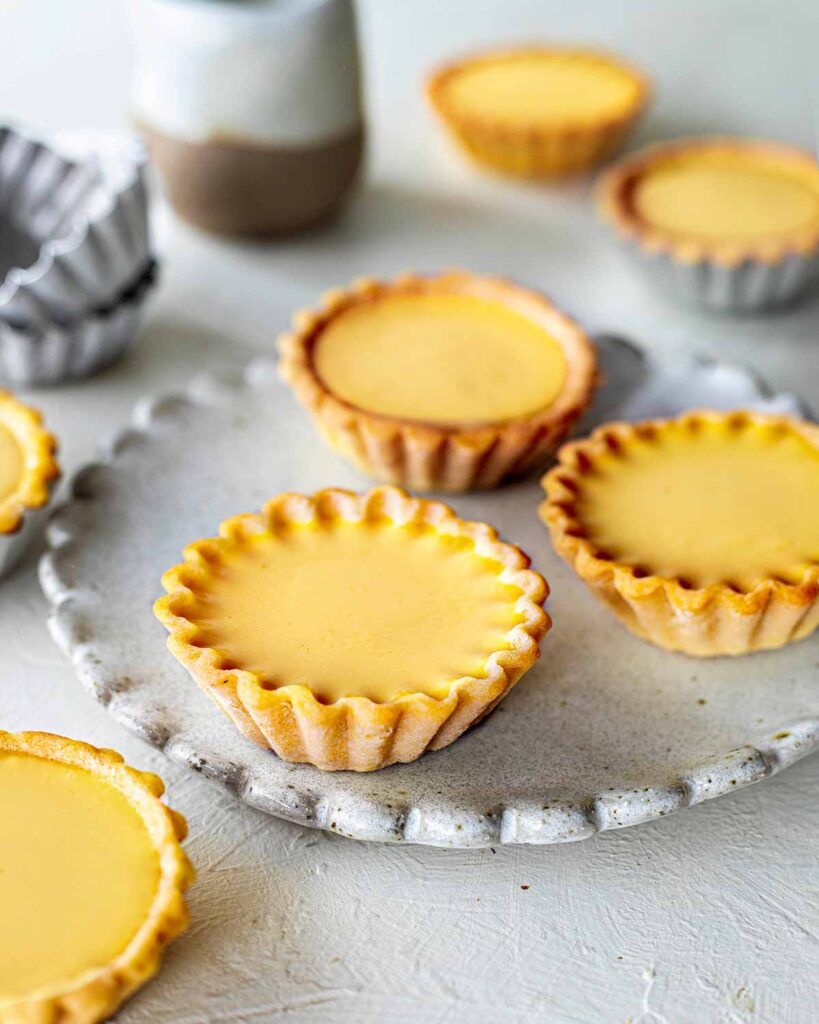 Multiple vegan egg tarts on a scalloped plate and around. Close up showing pretty crimped edges of one tart