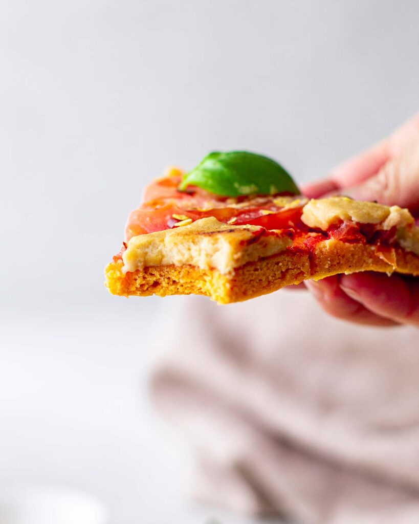 Close up of pizza slice showing fluffy texture of sweet potato base.