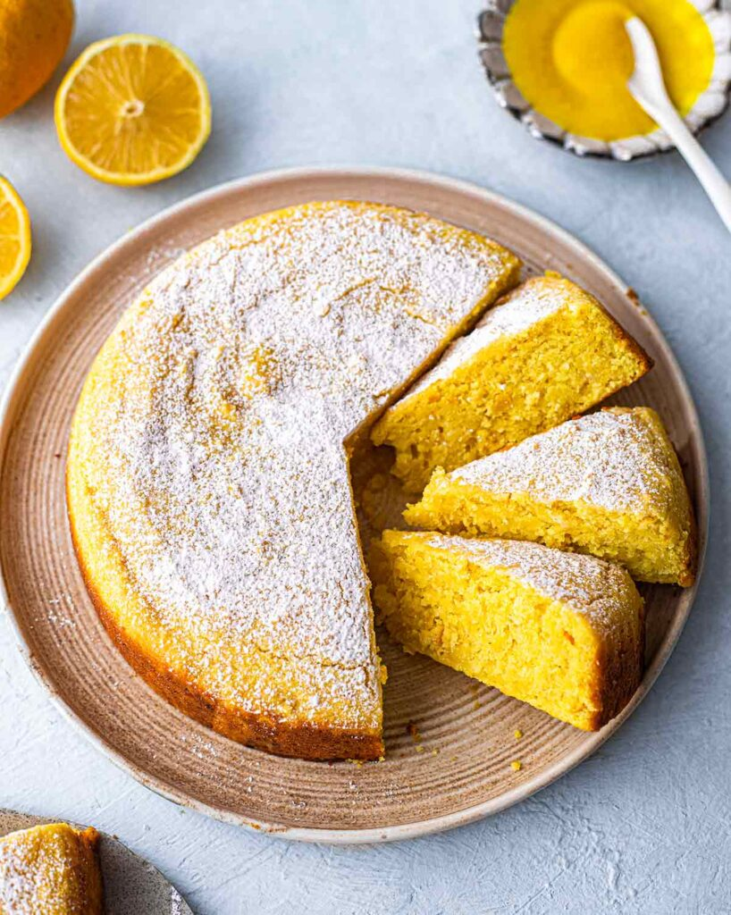 Whole vegan lemon cake on plate with slices coming out revealing bright yellow hue.