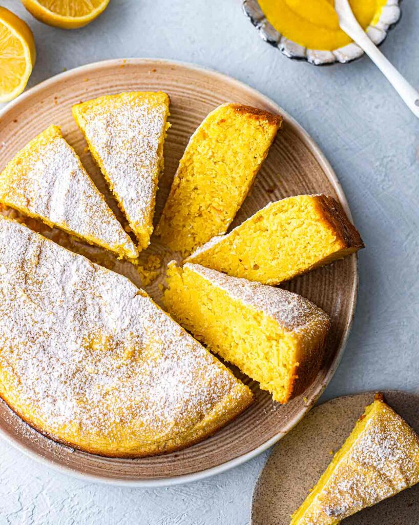 Top angle of whole vegan lemon cake on plate with slices coming out revealing bright yellow hue.
