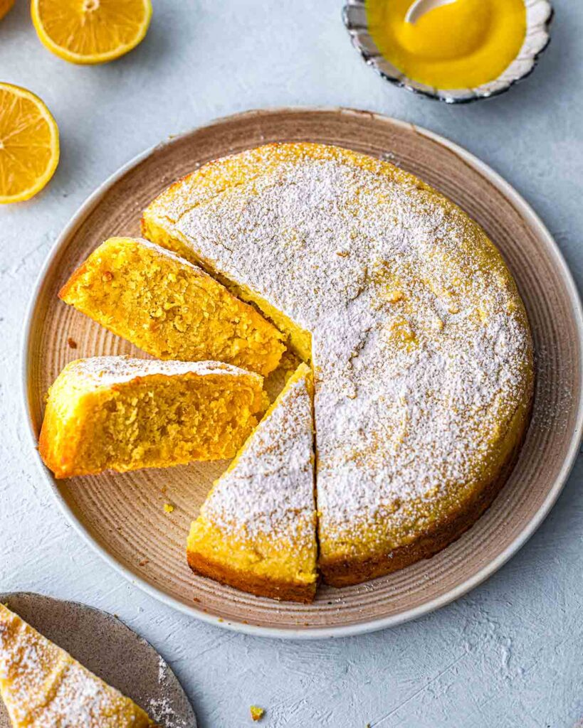 Lemon cake on plate with slices coming out revealing bright yellow hue.