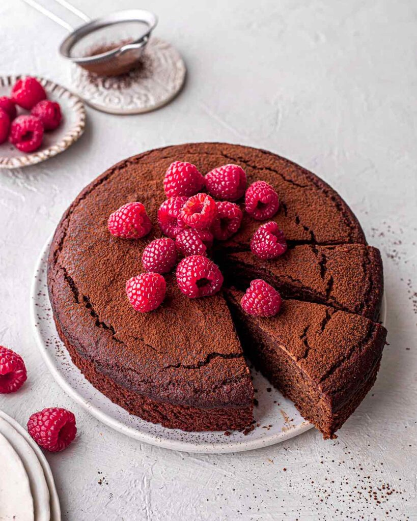 Flourless vegan gluten free chocolate cake on plate with a dusting of cocoa and fresh raspberries on top.