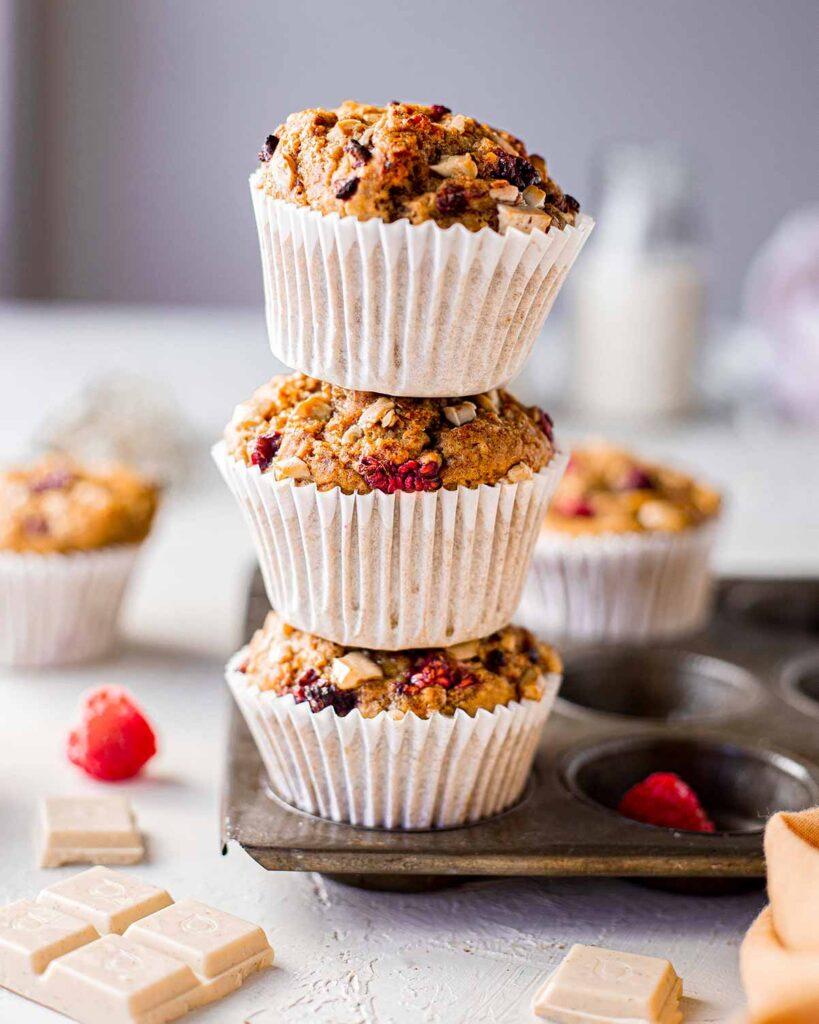 Stack of three vegan banana bread muffins with raspberries and white chocolate