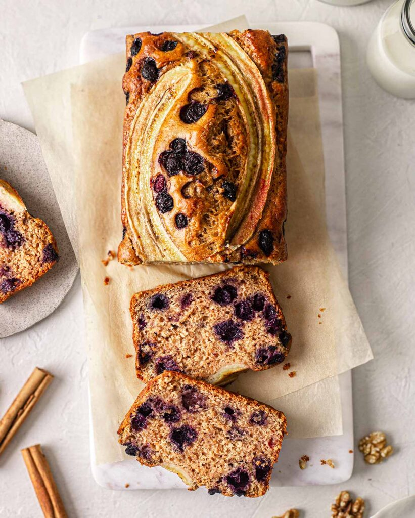 Overhead image of banana bread focusing on sliced banana and blueberry decorations.