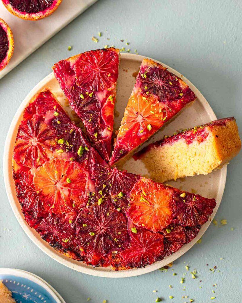 Upside down vegan blood orange cake on plate with a few slices cut out revealing golden fluffy interior.
