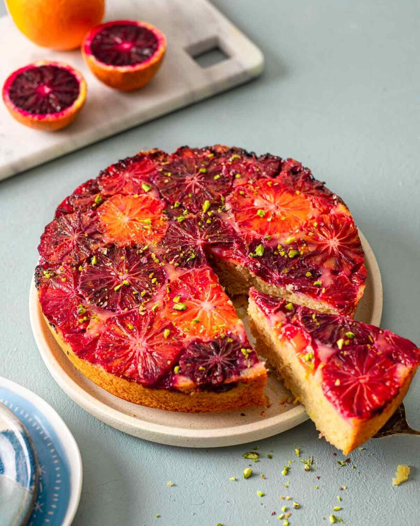 Cake on plate with one slice coming out focusing on orange and red hues of the blood oranges on top.