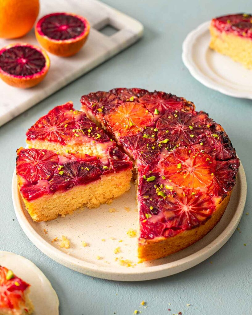 Blood orange cake on plate with a few slices cut out revealing fluffy golden cake.