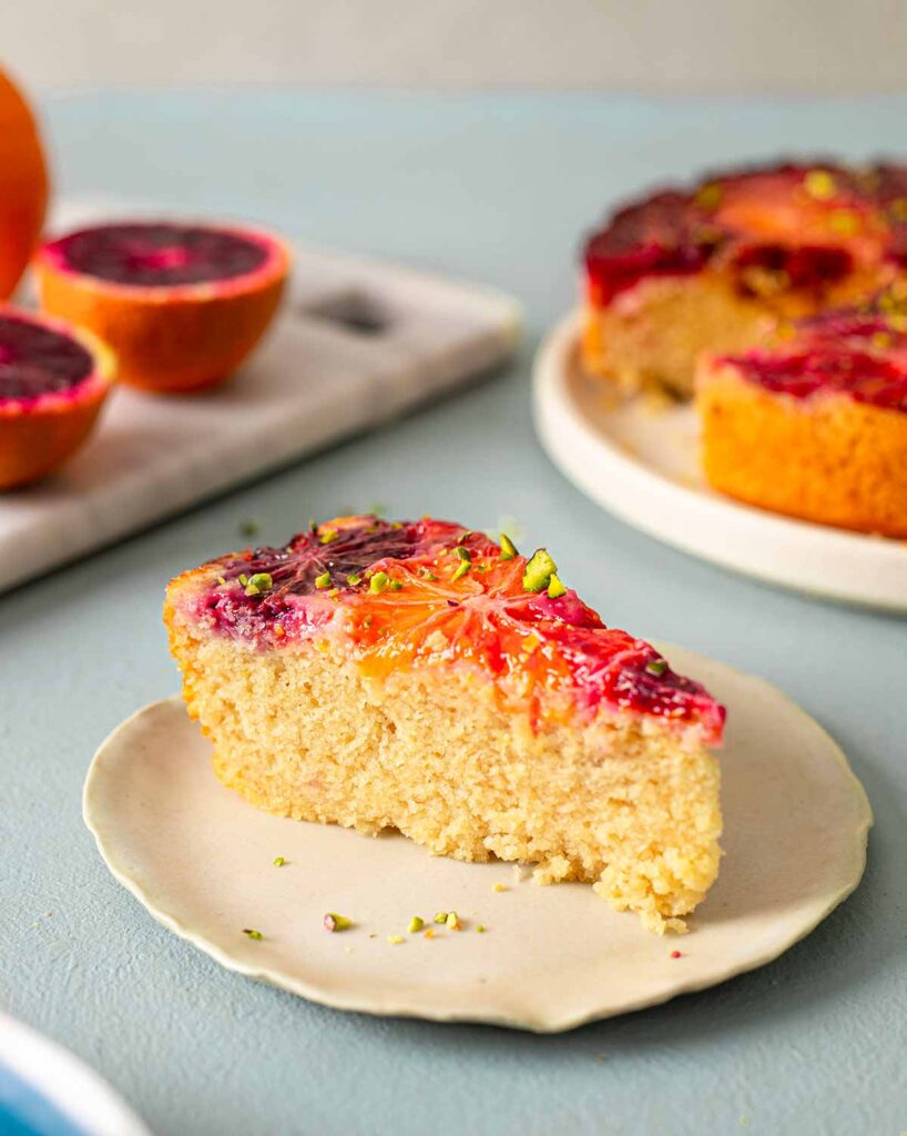 Close up of individual blood orange cake slice. The cake is golden and fluffy and has shiny blood orange slices on top.