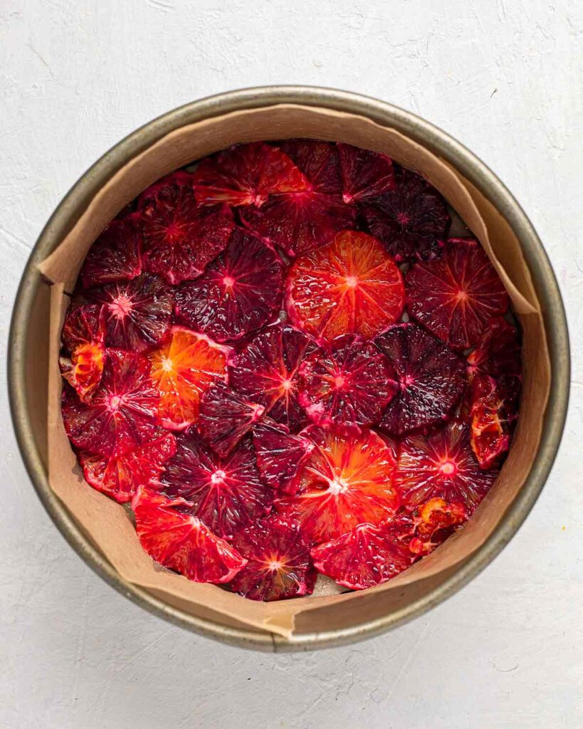 Overhead image of sliced blood oranges in bottom of lined cake pan.