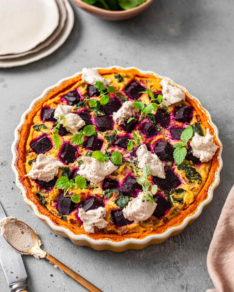 Vegan beetroot quiche in ceramic dish. The quiche has a bright orange pumpkin crust, golden filling and dollops of soft dairy free cheese.