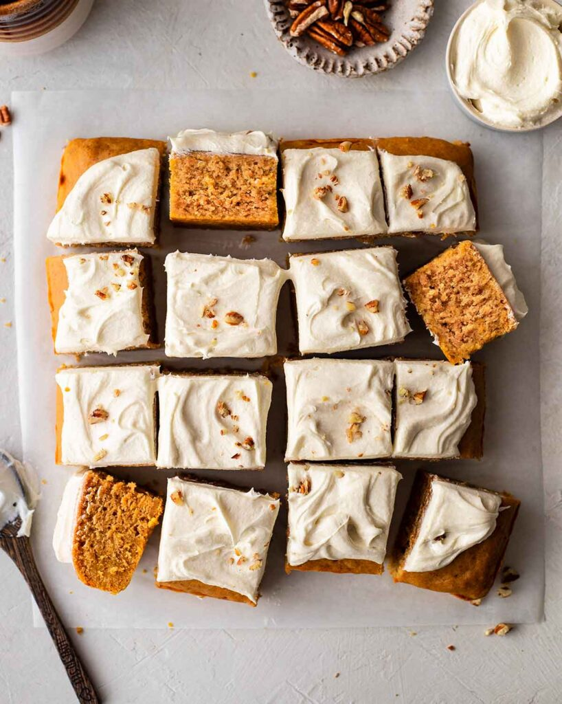 Flatlay of vegan sweet potato cake with creamy frosting cut into 16 squares.