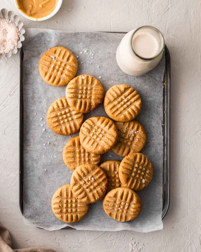 Peanut butter cookies on lined baking tray.