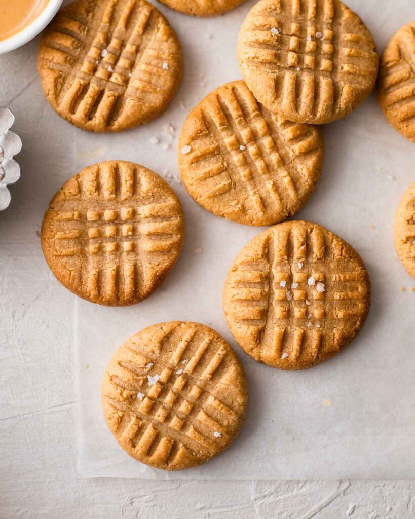 3 ingredient vegan peanut butter cookies with criss cross pattern and flaked salt on baking paper.