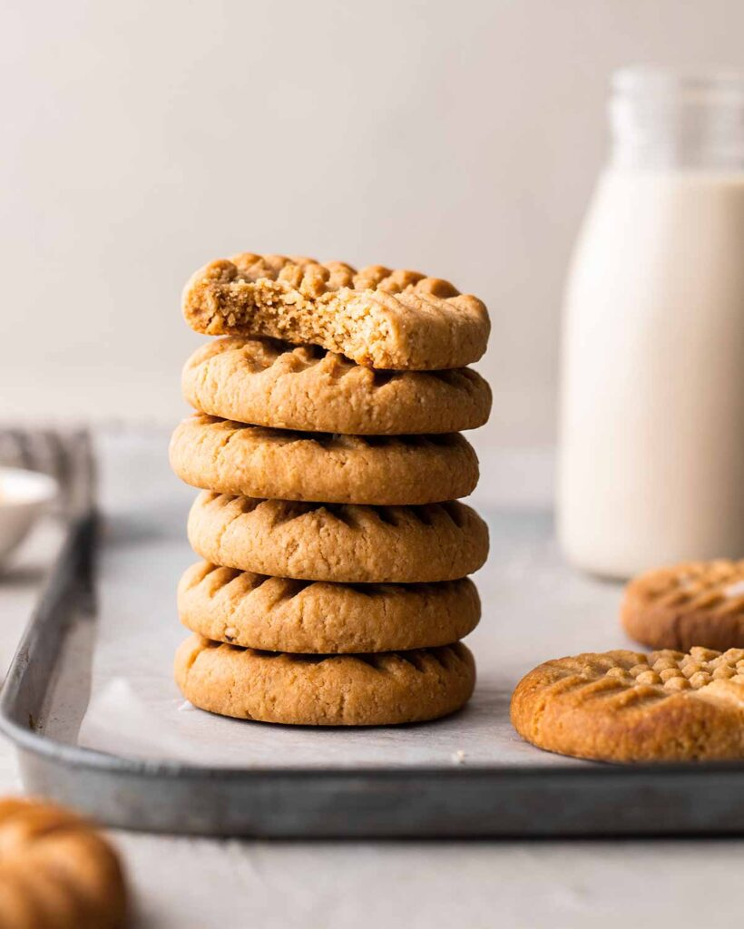 Stack of peanut butter cookies with bite taken out of one cookie revealing texture.