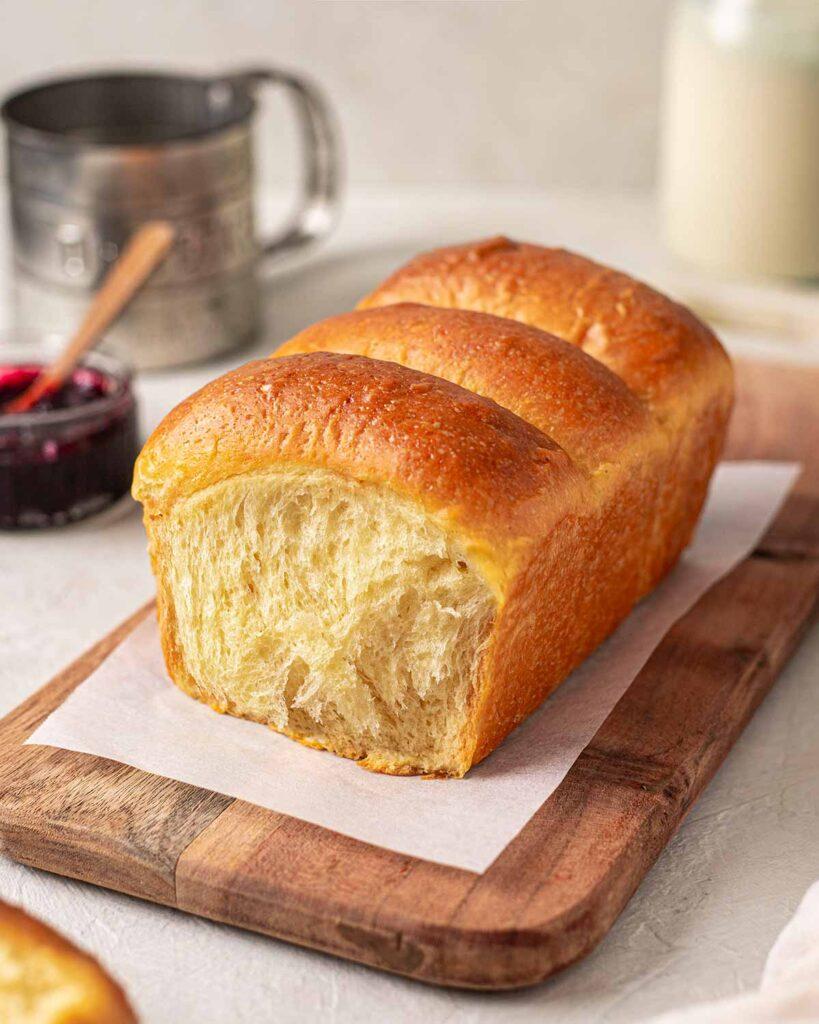 Buttery golden vegan brioche loaf on a serving board.