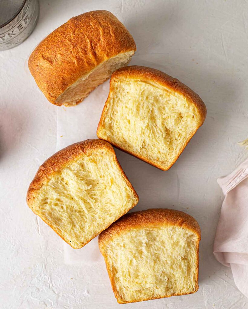 Flatlay of vegan brioche torn into 4 sections revealing fluffy and feathery interior.