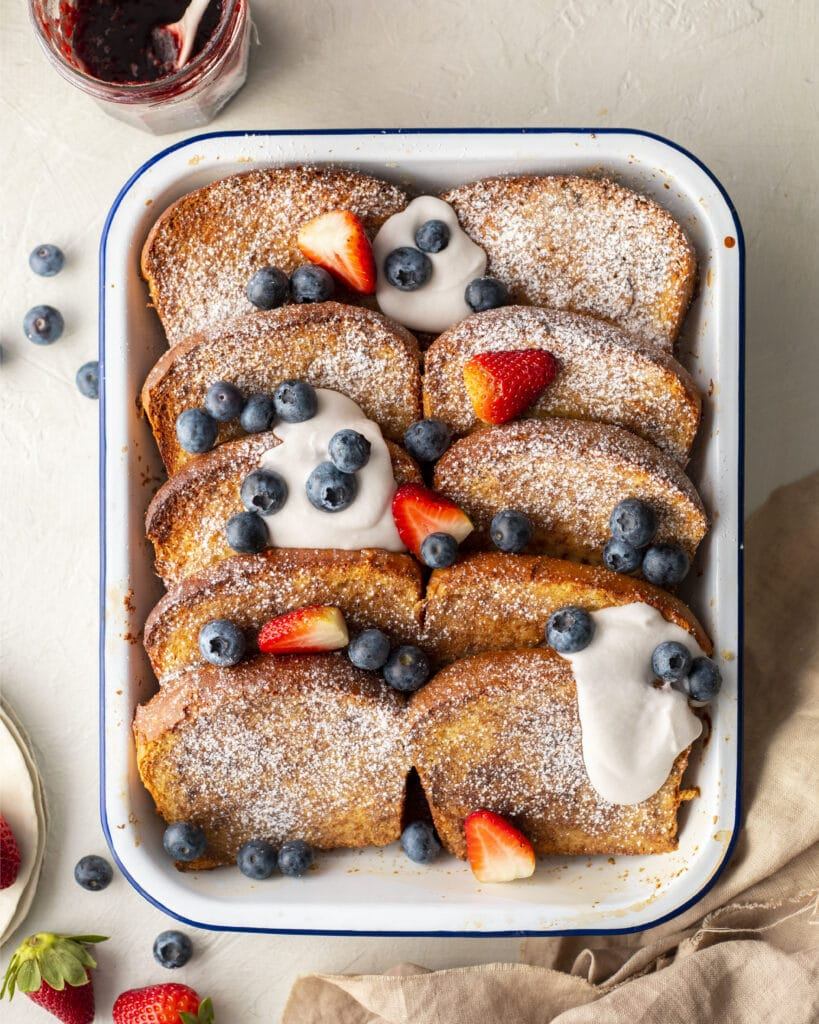 Baked vegan french toast where vegan brioche is cut into slices. The french toast are dusted with sugar and have cream and berries on top.