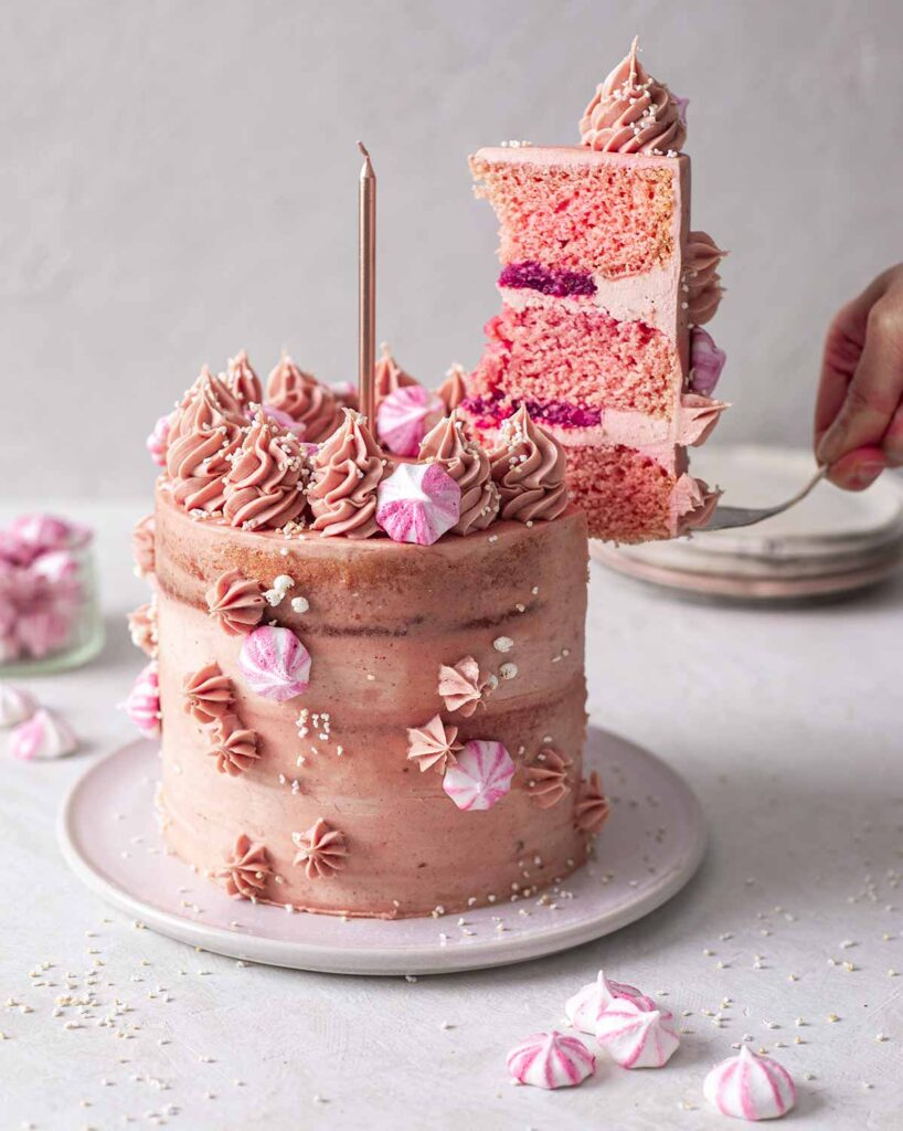 Pink vegan champagne cake decorated with pink buttercream, strawberry jam and meringue kisses. A slice is cut out of the cake and being lifted out.