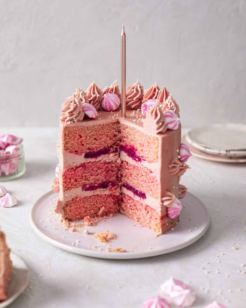 Cross section of cake revealing fluffy pink cake, layers of strawberry jam and baby pink buttercream.