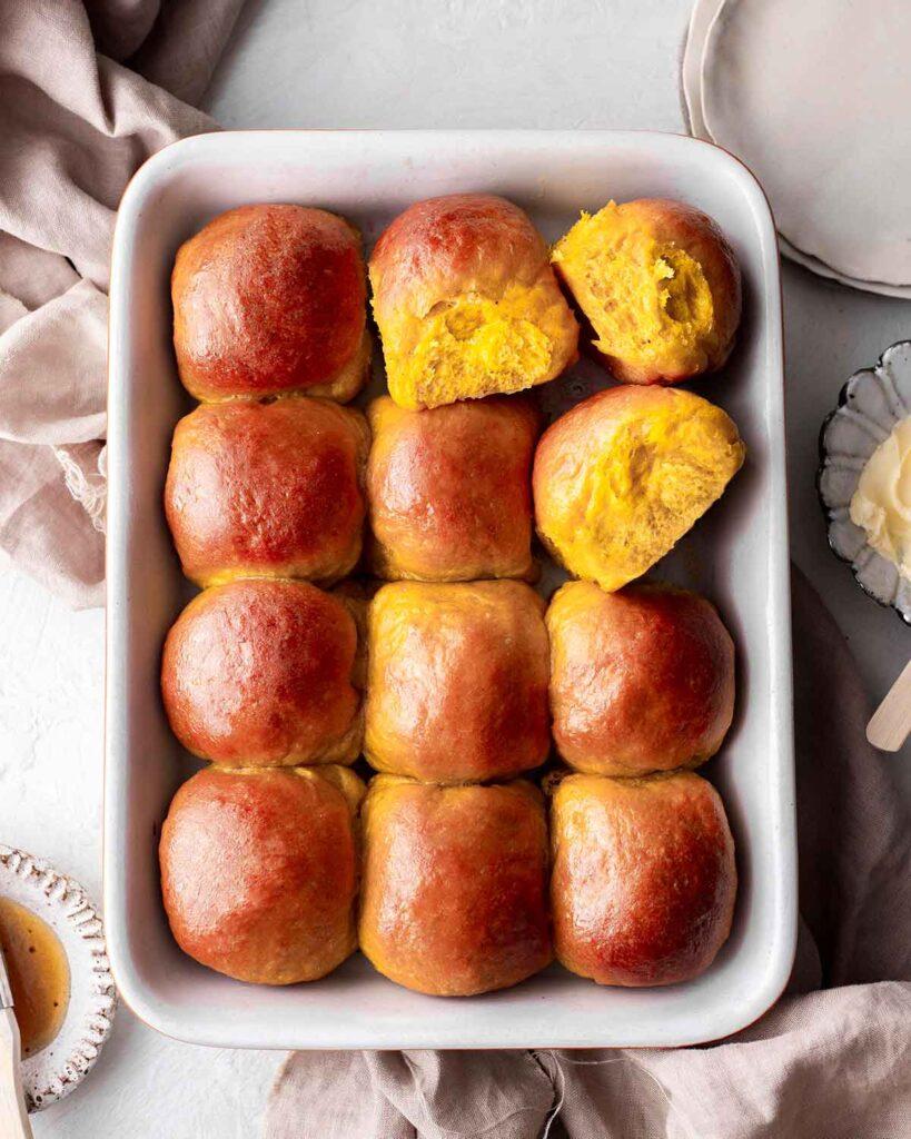 Dozen of golden pumpkin buns in baking tray.