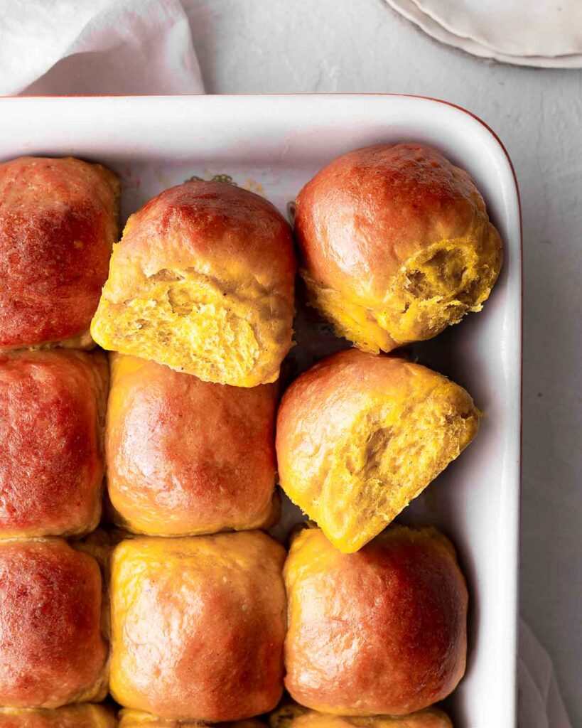 Close up of pumpkin dinner rolls in baking tray showing fluffy texture.