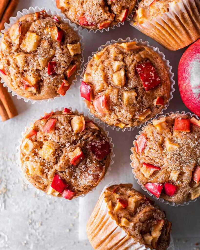 Flatlaye of apple muffins showing golden muffins tops, especially red apple chunks and granulated sugar.