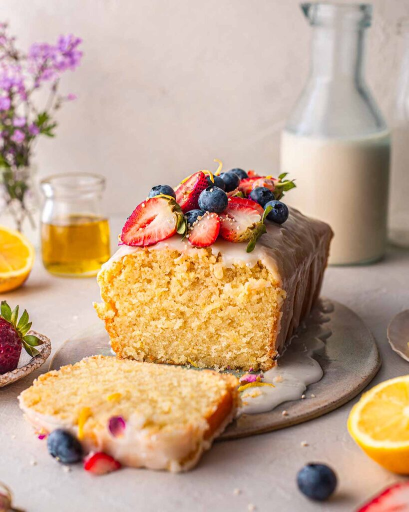 Lemon olive oil cake with a thin icing, blueberries and strawberries on top. Cake is on a plate amongst a few colourful items.