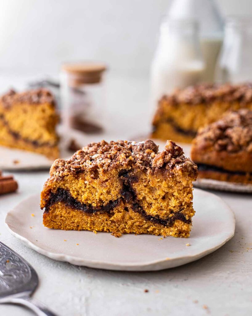 Close up of a slice of vegan pumpkin coffee cake showing thick cinnamon sugar swirl.
